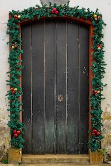 Vecchia struttura della porta di legno con ornamenti natalizi.