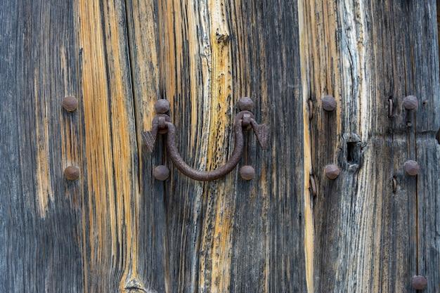 Vecchia porta in legno con maniglia in metallo invecchiato sfondo strutturato architettonico d