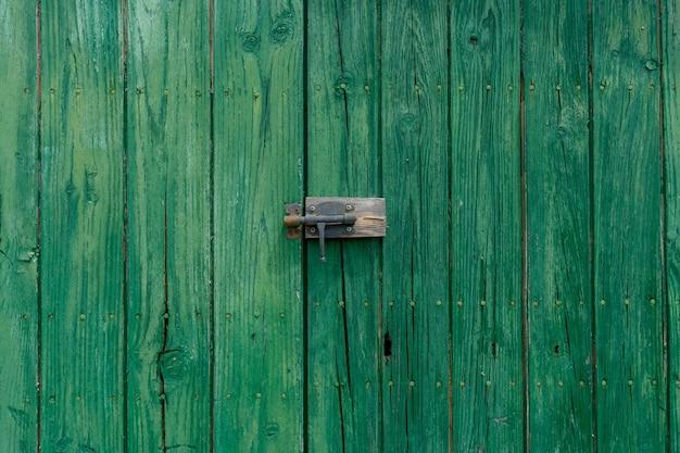 Vecchia porta di legno con fondo strutturato architettonico della maniglia della porta di metallo invecchiato