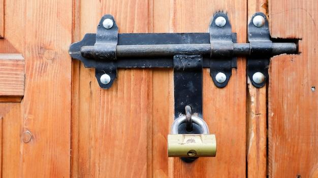 Vecchia porta di legno con un bullone di metallo nero. vista ravvicinata di una serratura e scrocco su una porta di legno. chiavistello in metallo rustico in legno. questo blocco scorrevole può essere utilizzato su tende da sole, scrivanie o recinzioni.