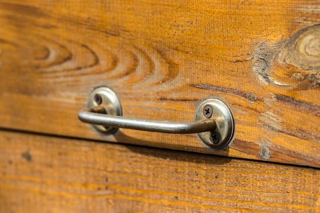 Vecchia porta di legno con una maniglia in background.