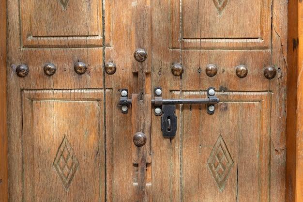 Una vecchia porta di legno con bullone metallico, vicino, dall'arabia