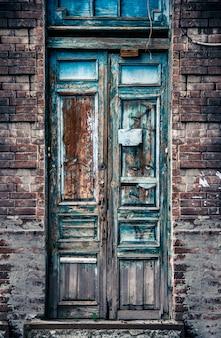 Vecchia porta di legno con vernice scrostata