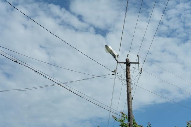 Vecchio palo elettrico in legno con una lampada e molti cavi che corrono in direzioni diverse, cielo nuvoloso.