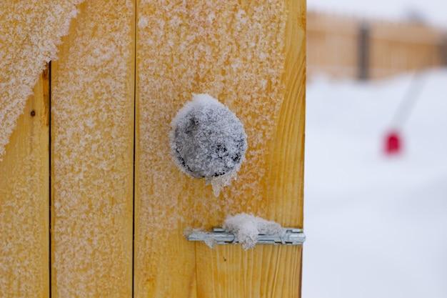 Vecchia staccionata in legno. sulla recinzione ci sono fiocchi di neve. trama e sfondo. tavola di legno. sulla recinzione ci sono fiocchi di neve. trama e sfondo. porte e maniglia della porta congelate