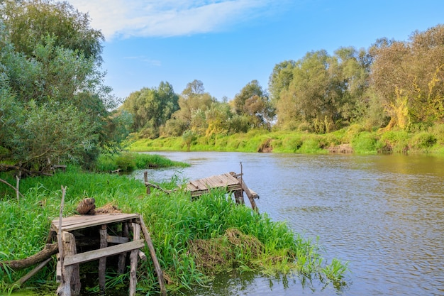 Vecchi ponti di pesca in legno sulla piccola sponda del fiume. paesaggio fluviale al mattino soleggiato autunnale