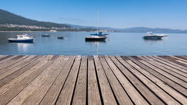 Vecchia passerella in legno in riva al mare con sfondo sfocato e barche