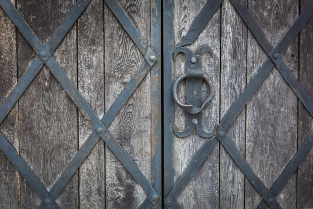 Un vecchio cancello di legno è decorato dalla grata forgiata