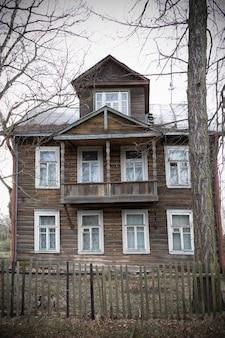 Vecchia casa in legno con soffitta e cornici bianche dietro una recinzione tra i rami degli alberi.