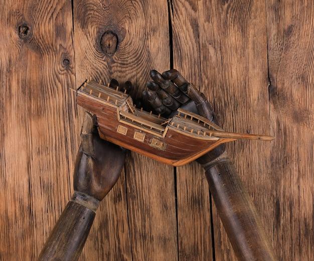 Manichino di legno vecchio mani su sfondo di legno