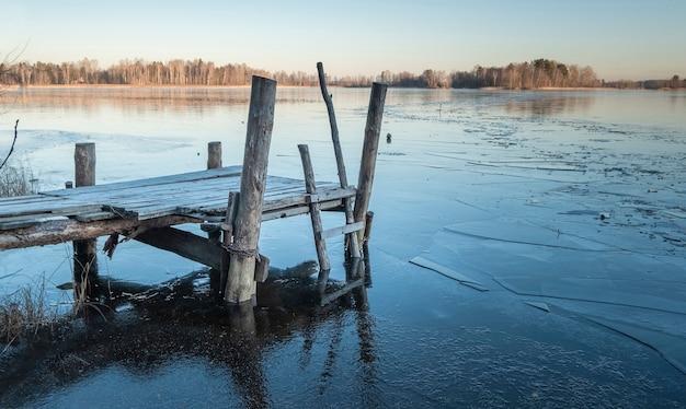 Vecchio molo in legno da un lago ghiacciato all'inizio della primavera in una giornata di sole