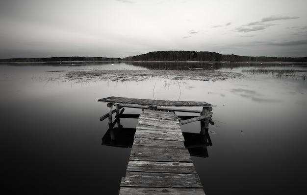 Vecchio molo in legno sul lago. bianco e nero
