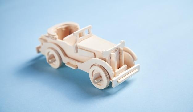 Vecchia auto giocattolo retrò in legno sullo sfondo blu.