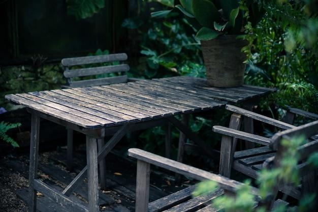 Vecchio insieme di legno per mobilia all'aperto in giardino tropicale, tavola del caffè