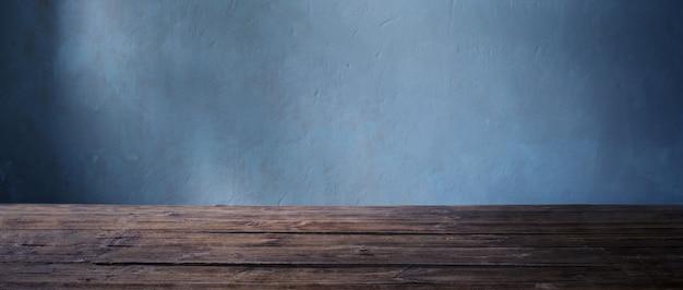Vecchia tavola di legno sulla parete di buio del fondo