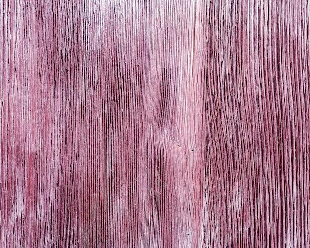 Vecchia struttura in legno di colore viola con crepa.