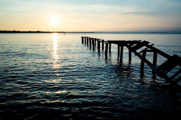 Una vecchia passerella di legno conduce nel lago con le sue assi rotte e consumate dal tempo.