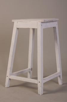 Vecchio sgabello in legno bianco su grigio