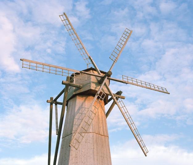Vecchio mulino a vento di legno isolato sul cielo nuvoloso blu