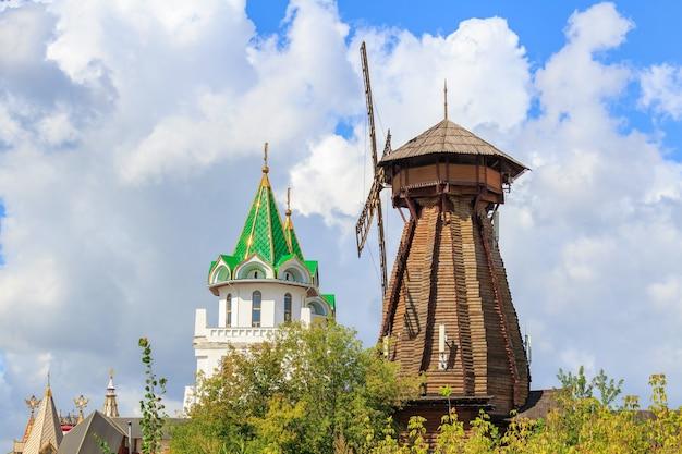 Vecchio mulino a vento in legno nel cremlino di izmailovo a mosca contro la torre di guardia nella soleggiata mattina d'estate