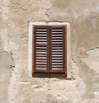 Vecchia finestra di legno in un muro incrinato