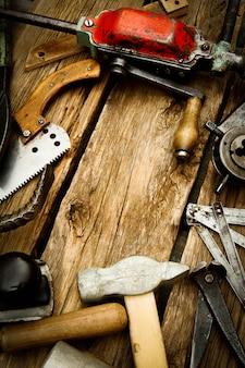 Vecchi strumenti di lavoro. strumenti di lavoro d'epoca (trapano, sega, righello e altri) su fondo in legno.