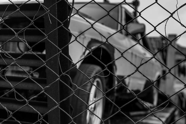 Vecchia scena distrutta dell'automobile in bianco e nero. automobile arrugginita abbandonata in recinto di filo metallico. camion abbandonato in decomposizione. vista dal recinto al camion.
