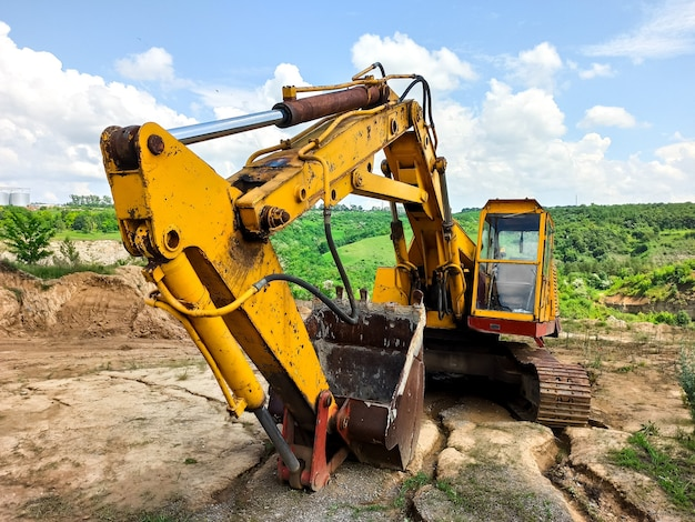 Un vecchio escavatore giallo è abbandonato in una vecchia cava.