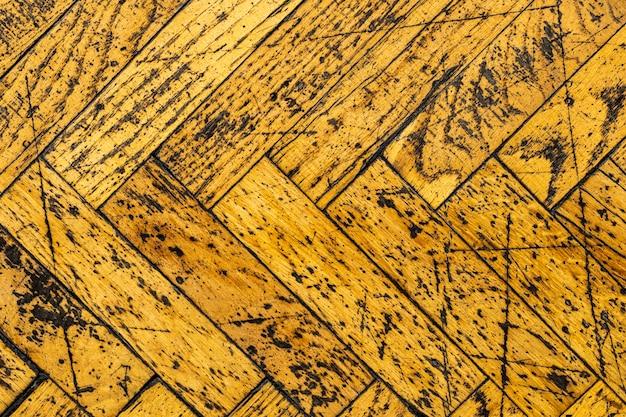 Vecchio parquet giallo in graffi. struttura in legno squallido. sfondo per il design. foto di alta qualità