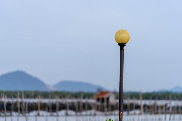 Vecchio lampione giallo sul palo di metallo nero con sfondo sfocato di montagne.
