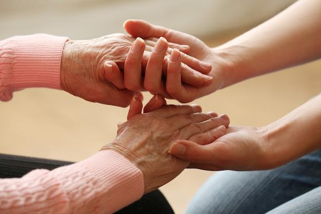 Vecchi e giovani mano nella mano su sfondo chiaro, primo piano