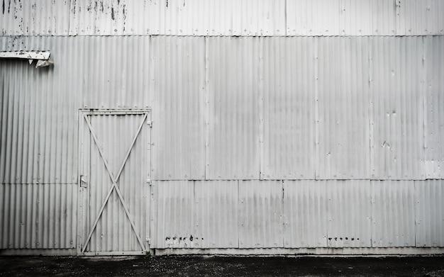 Vecchia parete sporca bianca del magazzino dello zinco e fondo della piccola porta