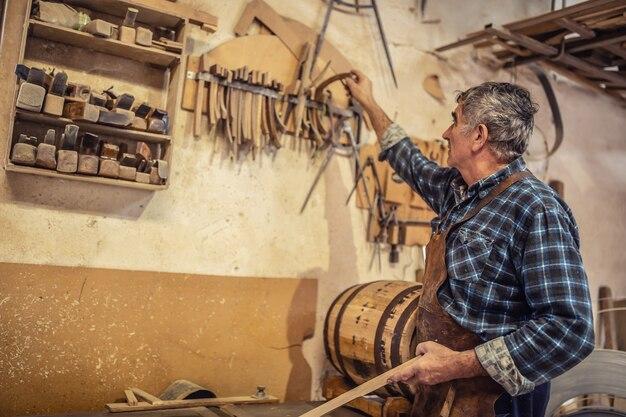 L'artigiano più anziano sceglie le parti necessarie per realizzare prodotti in legno in un laboratorio rustico.