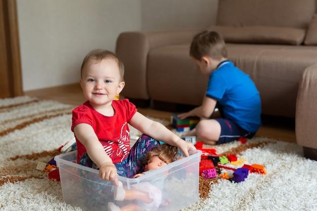 Il fratello maggiore sta giocando sul tappeto con il costruttore e la sorella è seduta in una scatola da sotto il costruttore.