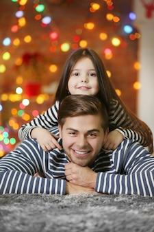 Fratello maggiore con la sorellina che si abbraccia nel soggiorno di natale