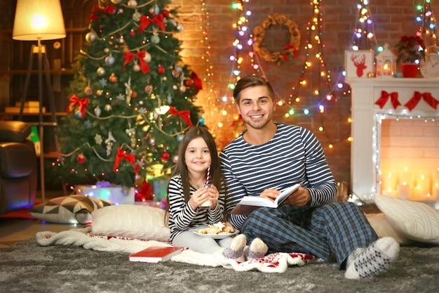Fratello maggiore con la sorellina che legge un libro e mangia biscotti nel soggiorno di natale