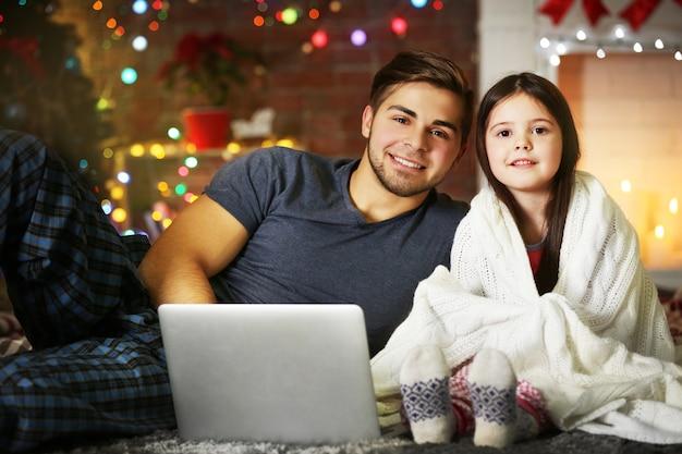 Fratello maggiore con la sorellina che usa il laptop nel soggiorno di natale
