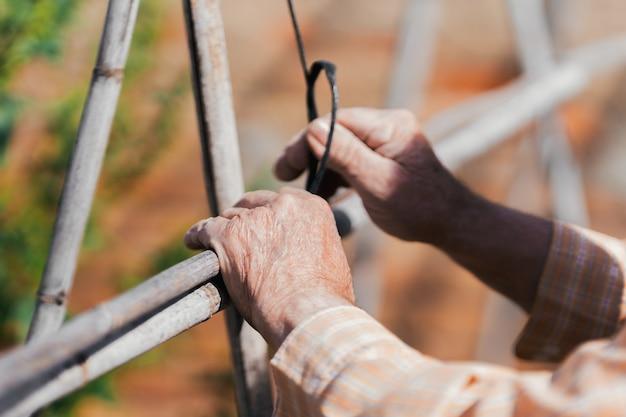 Uomo anziano che maneggia i materiali per costruire un orto