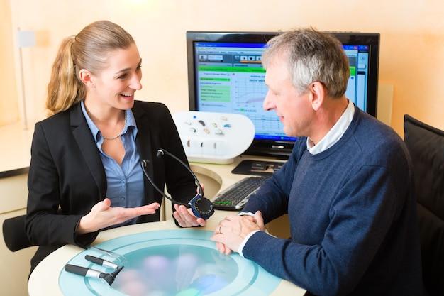 Un uomo anziano o un pensionato con problemi di udito effettua un test dell'udito e potrebbe aver bisogno di un apparecchio acustico