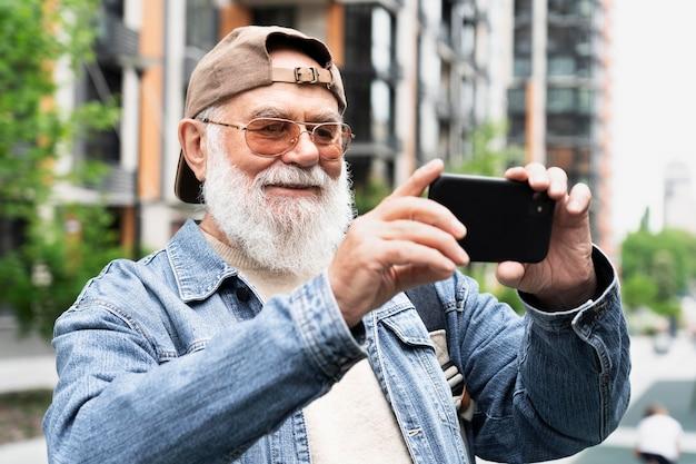 Uomo anziano che utilizza smartphone per selfie all'aperto in città