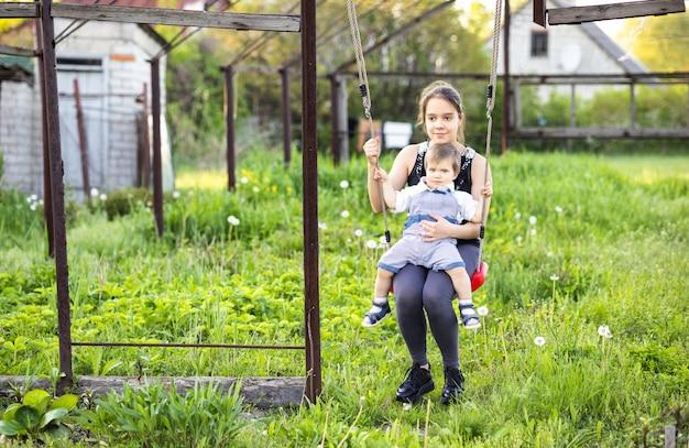 La sorella maggiore indossa abiti scuri primaverili e suo fratello minore è un bambino in tute luminose. lei lo cavalca su un'altalena rossa e si godono la primavera in un giardino fiorito nel caldo clima primaverile.