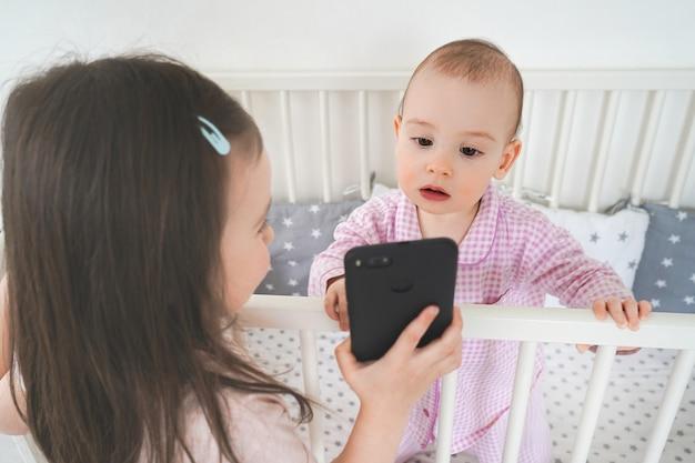La sorella maggiore fotografa la minore su uno smartphone. i bambini moderni usano i gadget.