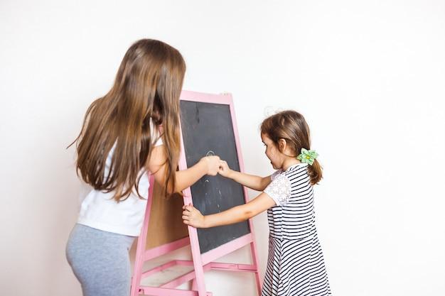 La sorella maggiore insegna più giovane alla lavagna