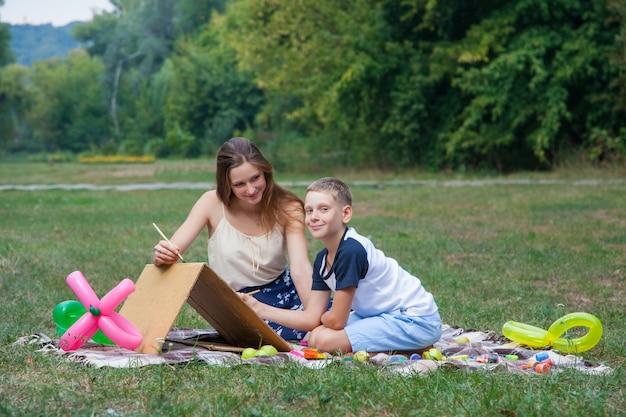 Sorella maggiore che cerca di insegnare a suo fratello a dipingere nel parco