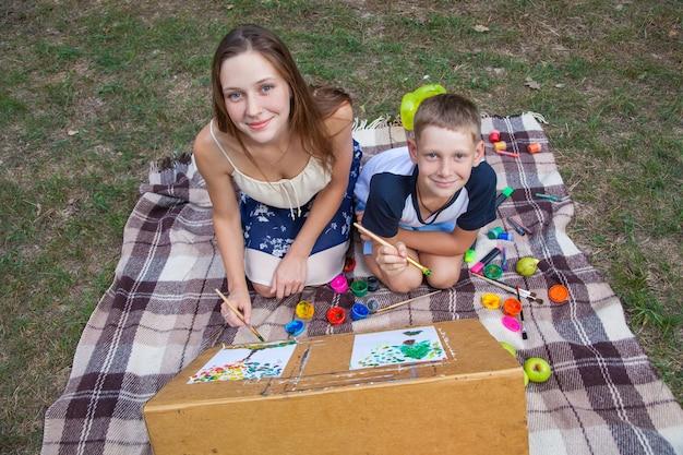 Sorella maggiore che cerca di insegnare a suo fratello a dipingere e posare nel parco in estate, guardando la macchina fotografica e sorridendo, disegnando e dipingendo..