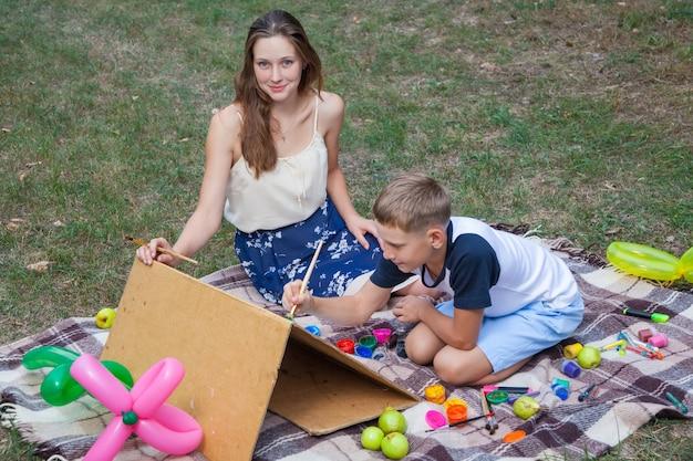 Sorella maggiore che cerca di insegnare a suo fratello a dipingere e posare nel parco in estate, guardando la macchina fotografica e sorridendo.