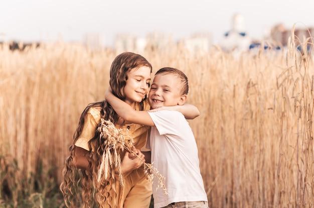 La sorella maggiore cammina con suo fratello nella natura in estate. bambini felici fratelli che camminano e giocano. i bambini giocano all'aperto