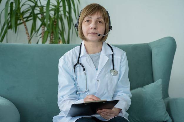 Terapista medico donna anziana che indossa la videochiamata della cuffia avricolare parlando con la webcam che consulta il paziente virtuale online