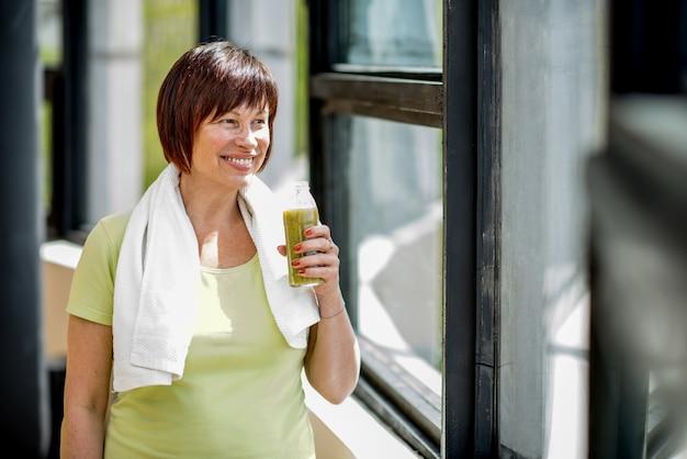 Donna anziana che beve frullato dopo l'allenamento al chiuso vicino alla finestra