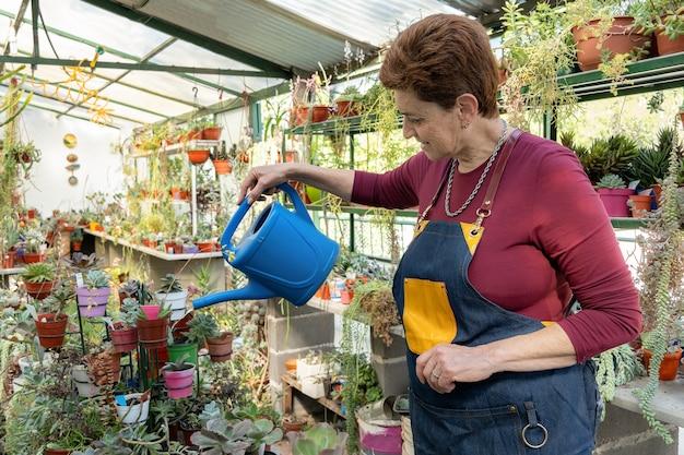 Donna anziana in grembiule da giardinaggio in posa con un annaffiatoio blu nella sua serra